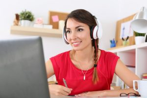 46188854 - beautiful smiling female student using online education service. young woman looking in laptop display watching training course and listening it with headphones. modern study technology concept